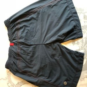 Grey lululemon men's shorts with red stitching.